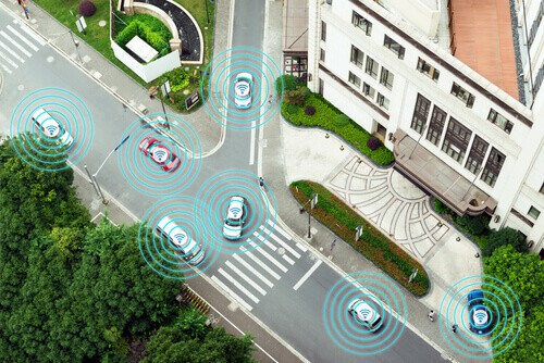 several cars in autonomous self-driving mode on metro city road iot concept